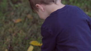 Little blond boy walking on grass outside with cute clothes as camera follows him hand held in slow motion.