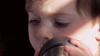 Little blond boy with big blue eyes looking at camera lens while reading book and drinking from a sippy cup extreme close up