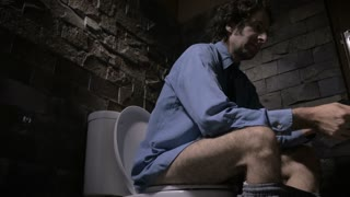 Low angle dolly shot of a man in a dress shirt loosening his tie while sitting on the toilet. He is visibly upset, distressed, or bothered about something.