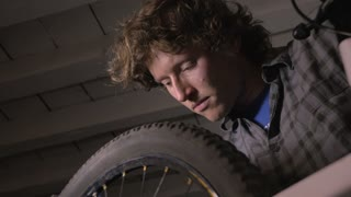 Low angle of a millennial man bike mechanic working on a bicycle wheel