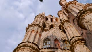 Low angle pan of the Parroquia in the Jardin in San Miguel de Allende against a bright blue sky