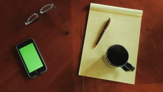 Man drinks coffee and grabs glasses at desk with yellow legal pad notebook, pen, and green screen on mobile phone - overhead shot.