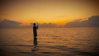 Man in prayer opens his hands to the sun and sky to receive the good grace of the lord while standing in a calm ocean at sunrise or sunset.
