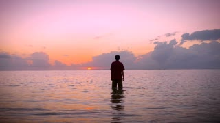 Man standing still in a calm ocean, raises his arms towards the sun in the early morning sunrise to a worship pose while looking up at the sky seeking answers and looking for inspiration.