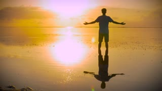 Man stands in stillness of the ocean with hands reaching out towards the sun in a worship pose seeking answers and looking for inspiration at sunrise or sunset with a beautiful reflection of himself in the water.