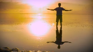 Man walks away after standing in stillness of the ocean with hands reaching out towards the sun in a worshiping pose looking at the sunrise or sunset with his reflection in the water below him.