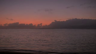 Man walks into frame and then stands in stillness on the ocean with hands to his side looking at early morning sunrise with colorful red and orange sky and clouds.