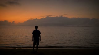 Man walks slowly into still ocean water as he faces a colorful early morning sunrise or late sunset surrendering to the awe-inspiring beauty of the world.