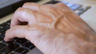 Man's hands typing on a QWERTY keyboard on a laptop computer - Close up.