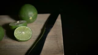 Medium continuous dolly shot of green and cut limes arranged on a wooden cutting board with a knife like a still life oil painting from the renaissance period.