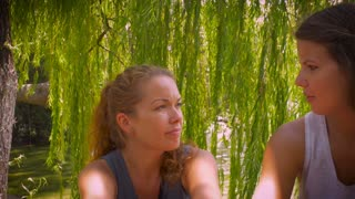 Medium dolly shot of two young attractive women talking to one another in a fun conversation while sitting outside under a tree by a water pond or lake on a bright summer day.