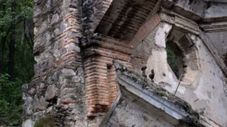 Medium shot pan of a church destroyed in an earthquake in Antigua, Guatemala showing some of the prior attempts at rebuilding in this seismically active zone