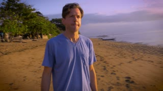 Middle aged young man on vacation motions with his hands to the camera operator to stop filming him while they stand on the sand at a beach with the ocean in the background.