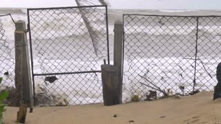 Ocean waves come crashing through a closed gate during a storm representing melting polar ice caps and rising sea levels