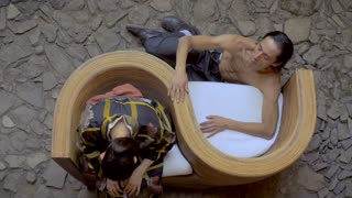 Overhead dolly shot of two butoh modern dancers doing a routine where the man is touching the back of the women slowly and controlling the movements in a curved chair on a stone floor.