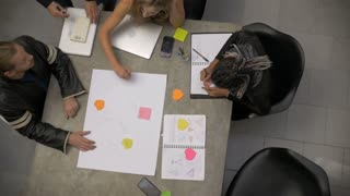 Overhead of a mixed race group of millennials collaborating and brainstorming together in slow motion writing on a large piece of paper with colored note pads.