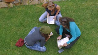 Overhead of three teenage girls studying and reading books on the green grass in slowmo