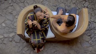 Overhead shot of a shirtless Mexican man touching a Japanese butoh dancer's face to court her in a traditional dance while sitting in a serpentine chair opposite of one another.