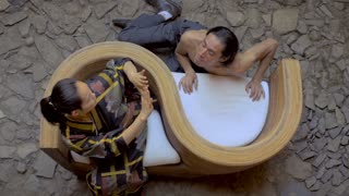 Overhead shot of two traditional butoh dancers - one shirtless - one is blowing kisses to his Japanese partner while she freaks out in fast sharp movements.