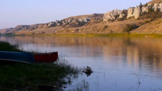Pan from two canoes on the banks of the Missouri River to the white cliffs in Montana along the Lewis and Clark national historic monument