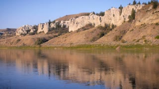 Pan up stream along the Missouri River revealing the white cliffs in Montana on the Lewis and Clark Monument