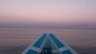 Peaceful footage of the bow of a boat turning on a calm and placid ocean or lake during sunrise or sunset