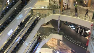People shopping in a mall with escalators on multiple levels