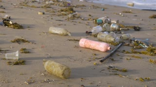 Plastic bottles littering the coast line of a deserted beach and in the ocean