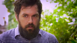 Portrait of a bearded man showing fear, paranoia, and anxiety as a man walks by