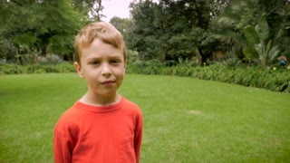 Profile of a young boy looking mischievous, innocent, or guilty - slowmo handheld