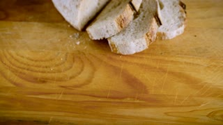 Push in of a baguette sliced into 3 slices on a wooden cutting board