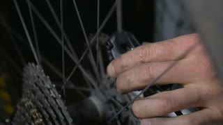 Push in of a bicycle mechanic adjusting disc brakes with greasy hands