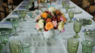 Push in of a floral center piece on a large dinning room table ready for a big celebration passover seder dinner.