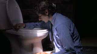 Push in of a man feeling ill, sad, or depressed while leaning up against a toilet. He is sitting on the floor with his arms around the porcelain bowl