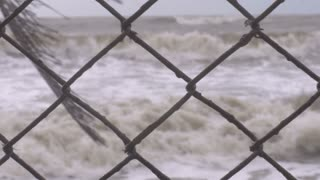 Rack focus of rough seas and large waves close to a rusty chain link fence representing loss of property due to climate change and raising sea levels