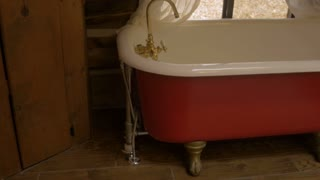 Red and white claw foot tub in a log cabin with white curtains and a window looking outside to dead leaves - pan up dolly shot