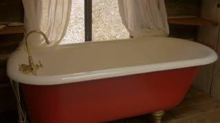Red and white claw foot tub with a gold faucet in a bathroom with a window revealing dead leaves outside - dolly shot