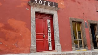 Red wooden door with white hotel sign against a red wall and a wooden hotel sign above the doorway