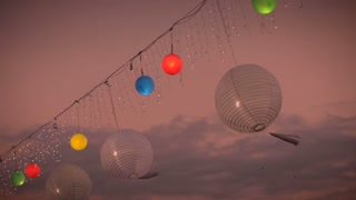 Red, yellow, green, blue, and white round lanterns and globes gently blow in the wind against the colorful sky of dawn or dusk at a festival, party, or festivity in slow motion.