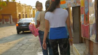 SAN MIGUEL DE ALLENDE - CIRCA MAY 2016 - A family of four young girls walk down the street during the day - steadicam shot in slow motion.