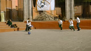 SAN MIGUEL DE ALLENDE, MEXICO - CIRCA MAY 2016 - 5 young boys play soccer in a plaza all wearing the same outfit.