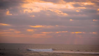 Several surfers surfing in the ocean during a magic hour sunset while rays of sun come through the clouds.