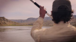 Shot behind a man paddling down the Missouri river in Montana with a kayak paddle with mountains in the background wearing a green baseball hat.