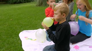 Side view handheld slowmo of a family of four blowing up balloons outside in a park like setting