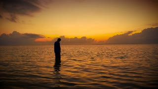 Silhouette of man standing in a calm ocean praying and/or meditating at sunrise or sunset while he is looking for answers and salvation.