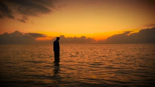 Silhouette of man standing in ocean in prayer during colorful sunrise or sunset
