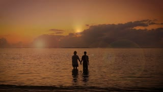 Silhouette of two adult people hold hands together and raise their arms to the sky in the Ocean as the sun rises surrendering to the good grace of the lord.