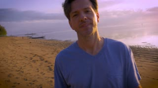 Single middle aged young man standing on beach does silly things like waves hand in front of camera in a playful manner on a sunny day with the sun and ocean behind him with a hand held home movie video feel.
