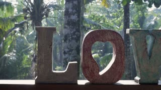 Slider shot of the word love on a railing overlooking a lush tropical jungle in Ubud, Bali. A slice of paradise on an island with palm trees and a rain forest.