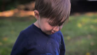 Slow motion and hand held shot of a portrait of a young little blond hair and blue eyed child smiling and walking in the grass, outside in a park or back yard of a private home.